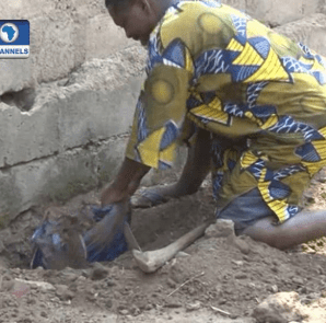 MR HOSEA FOLORUNSHO DIGGING UP HIS SON'S CORPSE FROM WHERE HE SECRETLY BURIED IT IN A SHALLOW GRAVE