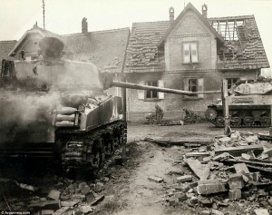 New territory: A tank moves through the ruins of a freshly retaken French town, while two medics attend to a fallen soldier on the roadside