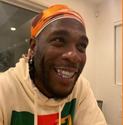 burna boy showing off his new teeth