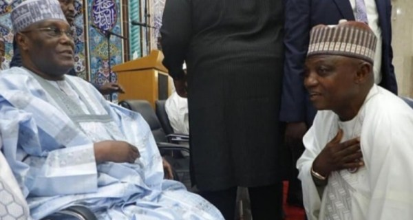 presidential spokesman, Garba Shehu while kneeling down to greet Atiku