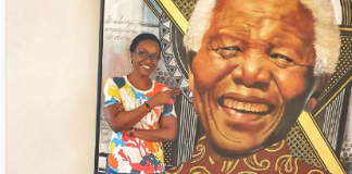 Kate Henshaw while standing close to late Nelson Mandele's portrait