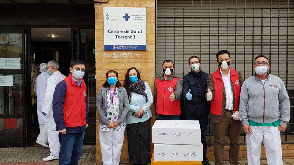 Los miembros de la comunidad católica china de Valencia entregando cajas con mascarillas y equipos de protección en centros de salud/AVAN