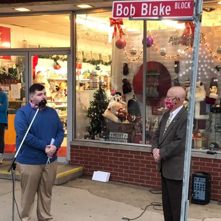 In November, the Village of West Union re-named the street in front of the pharmacy, Bob Blake Block.  Here, Councilman Jason Francis recognizes Blake for his many years of service as a former Mayor of the Village and local business owner.