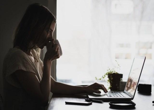 Mulher usando notebook e tomando café