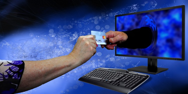A color photo that shows one hand passing a credit card to a hand in computer monitor – used to illustrate a point about how easily people trust websites