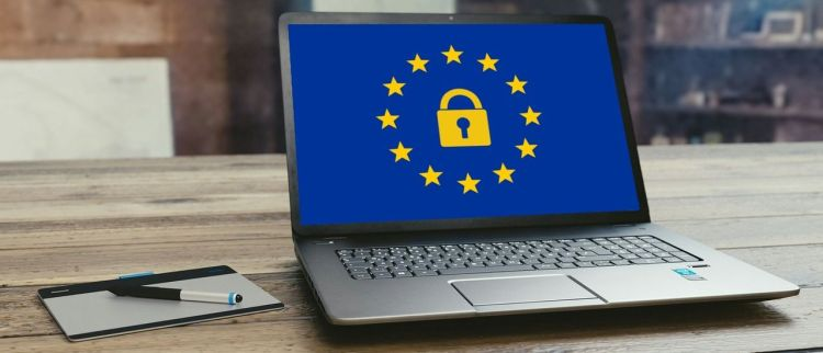 Color photo of a laptop on brown desk, with blue screen and gold European stars, used to illustrate a point about EU protecting people's digital rights.