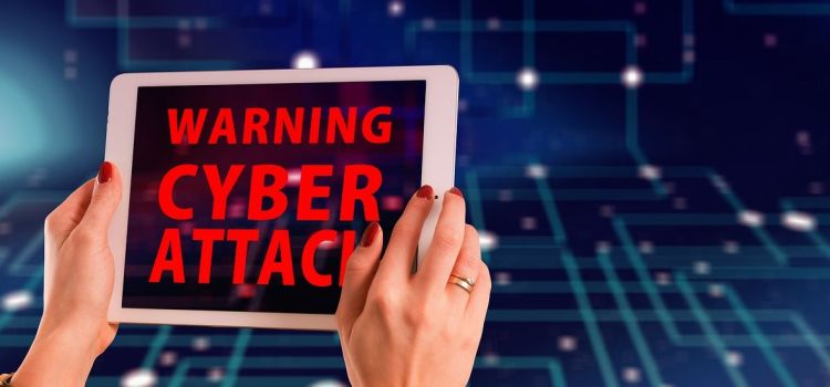 Color photo of a woman's hands holding a tablet with screen inscription: Warning Cyber Attack.