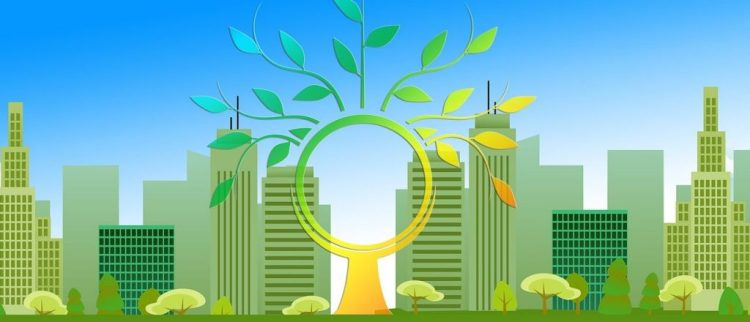 Color photo of a green city with the symbol of tree in front - used to illustrate the meaning of renewable energy and IoT.