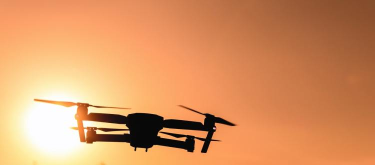 Color photo of a drone in air with sunset in background; used to illustrate the meaning of drones and privacy concerns.