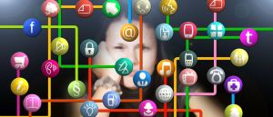 Color photo of mobile app icons, connected with stripes; with a confused woman in the background. Used to illustrate the meaning of Mobile App Security.