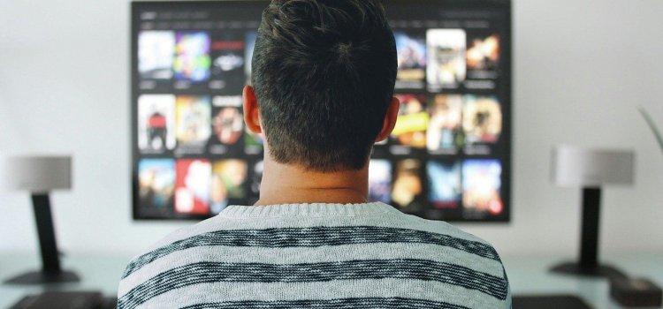 Color photo of a man watching a Smart TV - used to illustrate the prevalence of smart TVs.