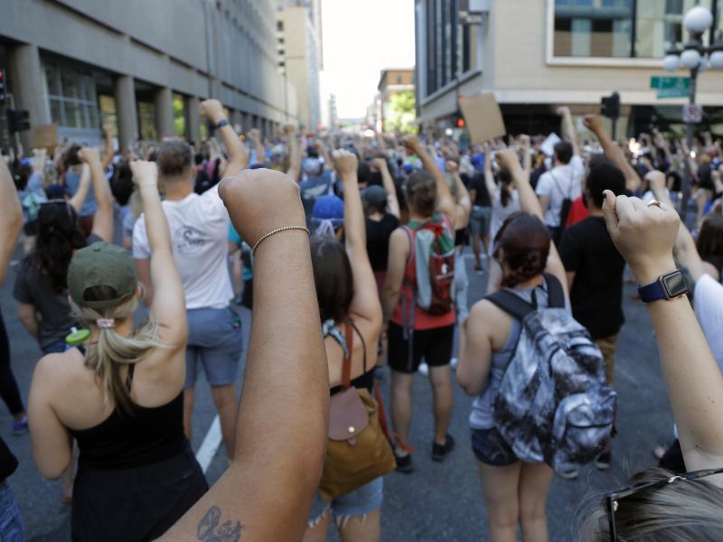 Demonstranten protestieren in der Nähe der Stadt Minneapolis und erheben solidarisch ihre Faust. Nach dem Tod des Afroamerikaners George Floyd bei einer brutalen Festnahme hat die Stadt Minneapolis erste Reformen ihrer Polizei auf den Weg gebracht. Foto: Julio Cortez/AP/dpa