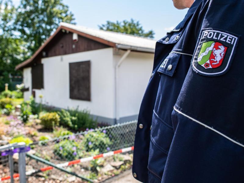 Ein Polizeibeamter steht vor der Gartenlaube in Münster, wo der vermutliche Haupttäter Teile seiner Server-Anlage unterbrachte. Foto: Guido Kirchner/dpa
