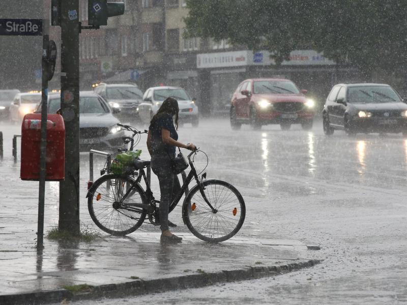 Eine Radfahrerin im strömendem Regen im Hamburger Stadtteil Wandsbek. Foto: Bodo Marks/dpa