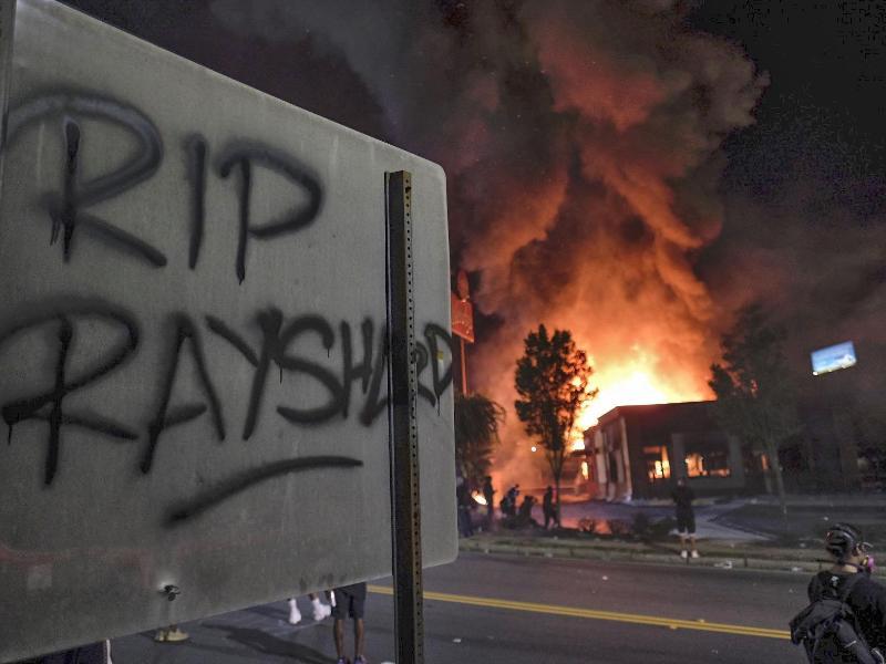 «RIP Rayshard» steht auf einem Schild, während im Hintergrund ein Wendy's-Restaurant brennt. Foto: Ben Gray/Atlanta Journal-Constitution/AP/dpa