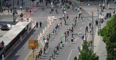Die Menschenkette in Berlin - hier in der Nähe des Alexanderplatzes - soll neun Kilometer lang sein. Foto: Jörg Carstensen/dpa