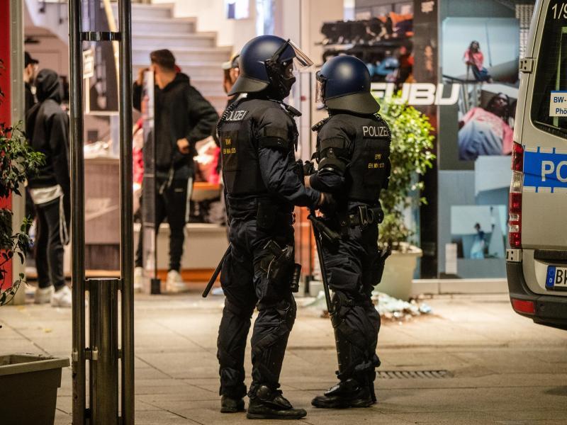 Einheiten der Polizei stehen vor einem zerstörten Geschäft. Foto: Christoph Schmidt/dpa
