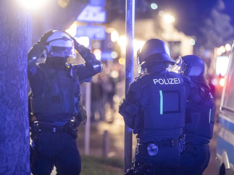 Polizeieinheiten sammeln sich, um gegen die Randalierer vorzugehen. Foto: Simon Adomat/dpa