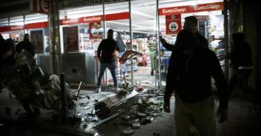 Menschen vor einem geplünderten Geschäft in der Marienstraße in Stuttgart. Foto: Julian Rettig/dpa