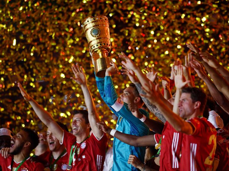 Münchens Torhüter Manuel Neuer hält die Trophäe jubelt mit demDFB-Pokal. Foto: Annegret Hilse/Reuters/POOL/dpa