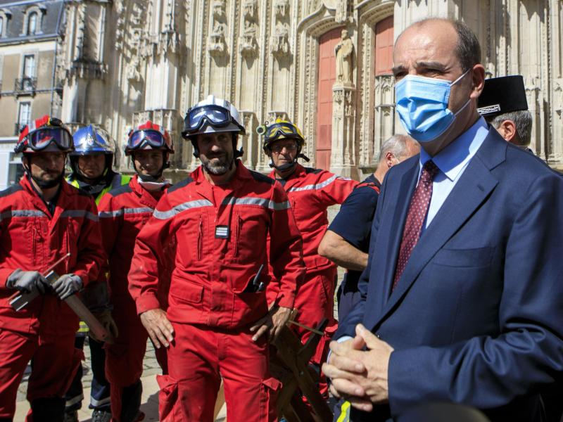 Der Premierminister von Frankreich Jean Castex trägt einen Mundschutz, während er sich mit Mitgliedern der Feuerwehr vor der Kathedrale Saint-Pierre-et-Saint-Paul trifft. Foto: Laetitia Notarianni/AP/dpa