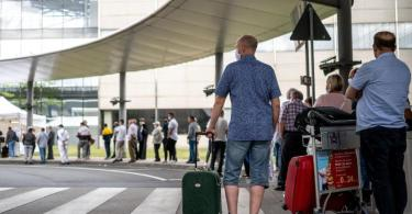 Reisende stehen am Corona-Testzentrum am Flughafen Köln/Bonn an. Foto: Marius Becker/dpa