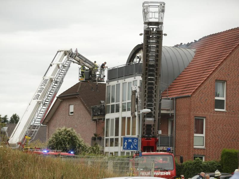 Feuerwehrleute nähern sich dem beschädigten Wohnhaus mit einer Drehleiter. Foto: David Young/dpa