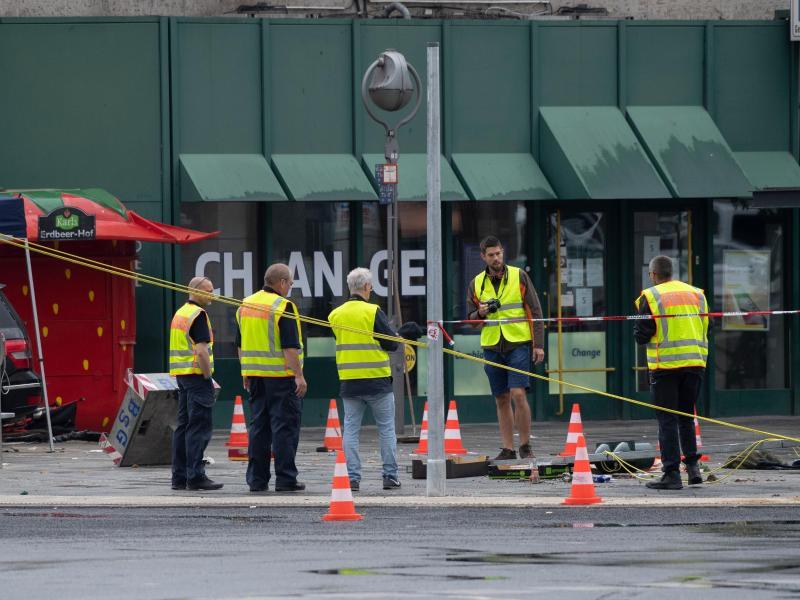 Polizeibeamte und Verkehrsexperten stehen nach dem Unfall am Bahnhof Zoo. Foto: Paul Zinken/dpa-zb-zentralbild/dpa