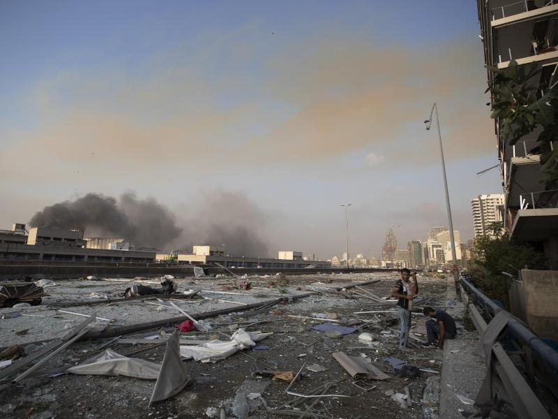 Zwei Männer stehen an einer mit Trümmern übersäten Straße. Foto: Hassan Ammar/AP/dpa