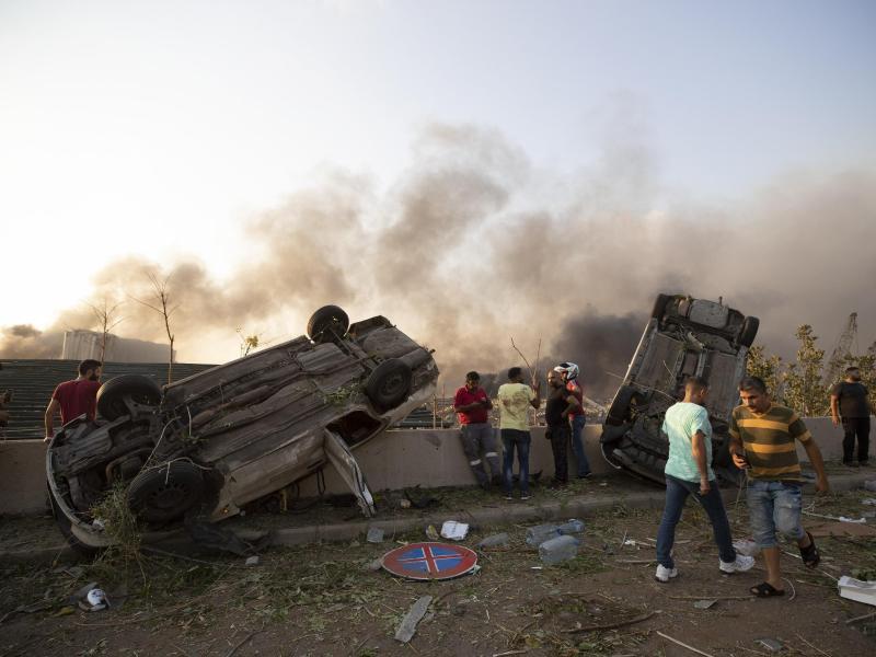 Von der Wucht der Explosion sind Autos umgekippt worden. Foto: Hassan Ammar/AP/dpa