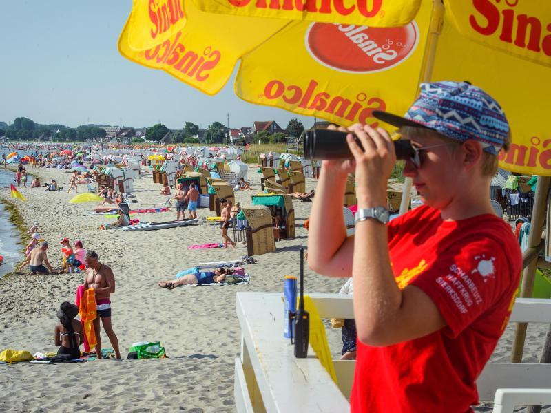 Eine DLRG-Mitarbeiterin beobachtet einen Strand in Scharbeutz an der Ostsee. Foto: Gregor Fischer/dpa