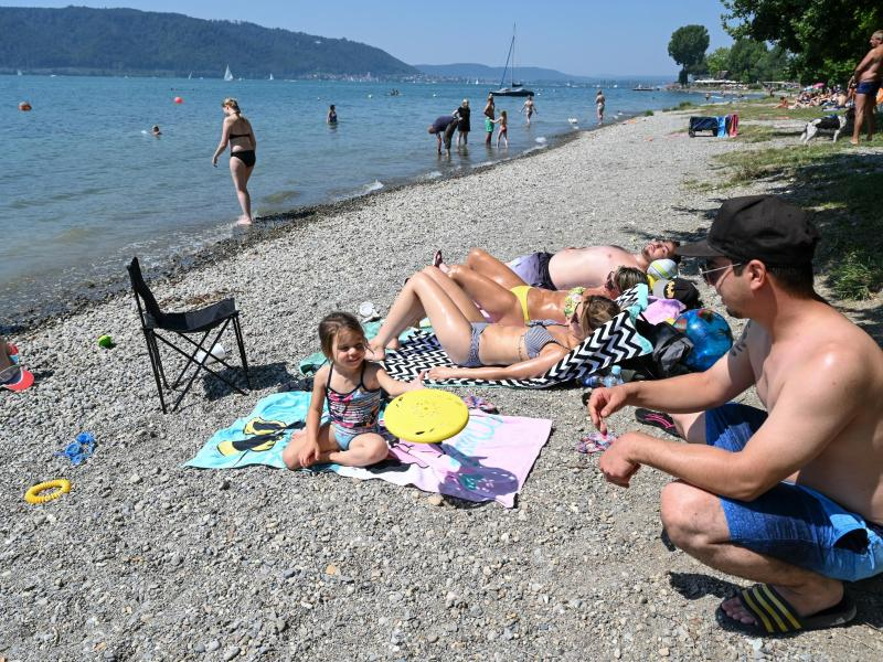 Eine Familie verbringt den Hitzetag am Ufer des Bodensees. Foto: Felix Kästle/dpa