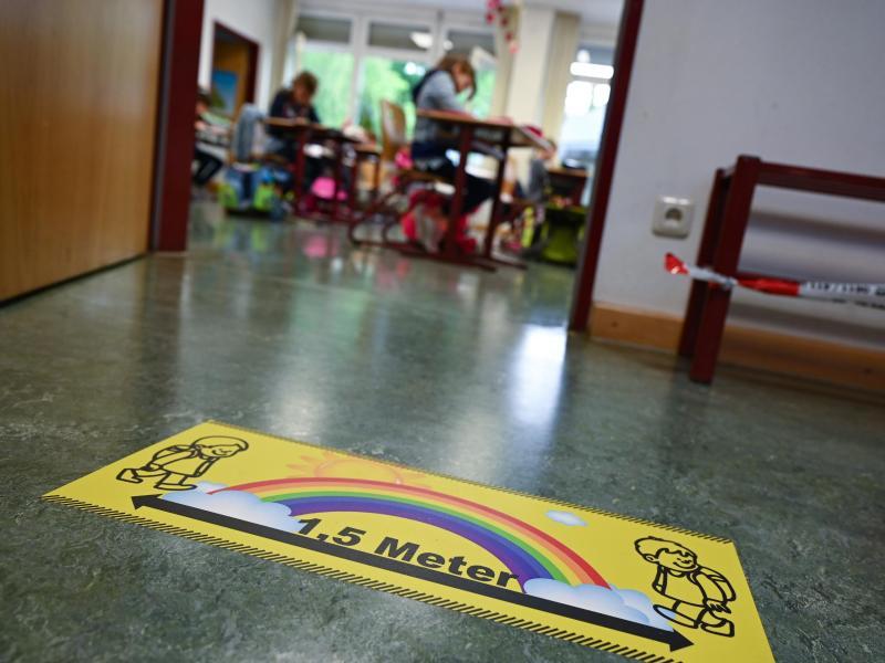 Ein Abstands-Hinweis klebt auf dem Fußboden einer Grundschule in Wiesbaden. Foto: Arne Dedert/dpa