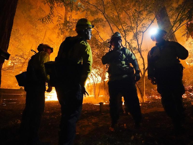 Ratlosigkeit: Feuerwehrleute besprechen das weitere Vorgehen der Löscharbeiten von einem Großfeuer bei Boulder Creek. Foto: Marcio Jose Sanchez/AP/dpa