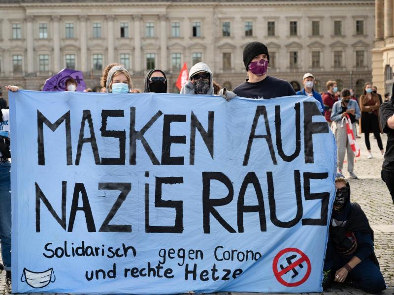 """Gegendemonstranten einer Kundgebung gegen die Corona-Maßnahmen sammeln sich und halten ein Banner """"Masken auf Nazis raus"""". Foto: Christophe Gateau/dpa"""