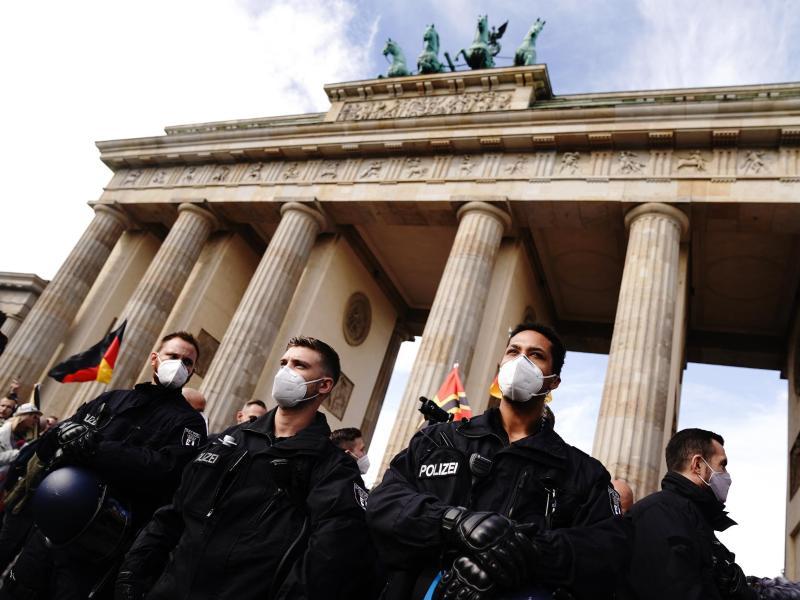 Polizisten mit Mundschutz vor dem Brandenburger Tor. Foto: Kay Nietfeld/dpa