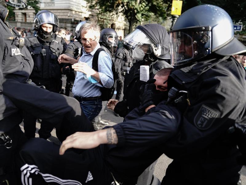 Die Polizei trägt einen Teilnehmer der Demonstration gegen die Corona-Maßnahmen in der Berliner Innenstadt weg. Foto: Kay Nietfeld/dpa