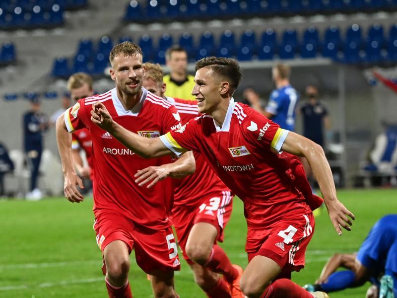Union setzte sich gegen Karlsruhe erst nach Verlängerung durch - Nico Schlotterbeck (r) traf in der 118. Minute. Foto: Uli Deck/dpa