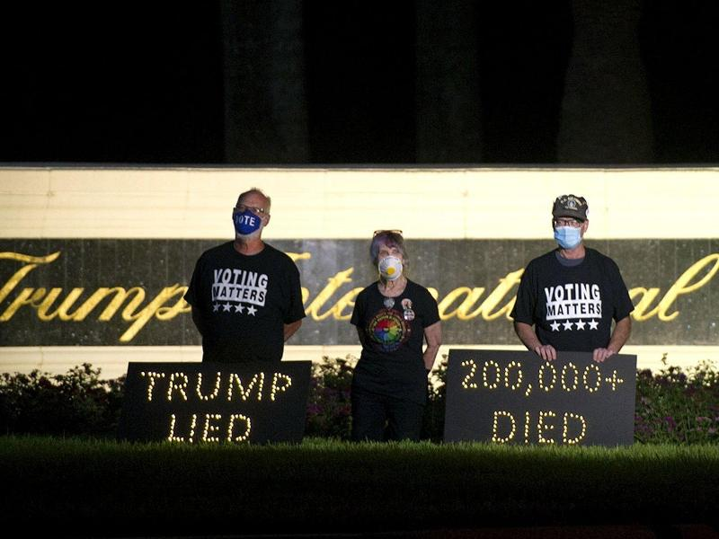 «Trump lied» - «200.000 died»: Demonstranten halten in der Nähe des Trump International Golf Club in Palm Beach eine Mahnwache ab. Foto: Meghan Mccarthy/Palm Beach Post via ZUMA Wire/dpa