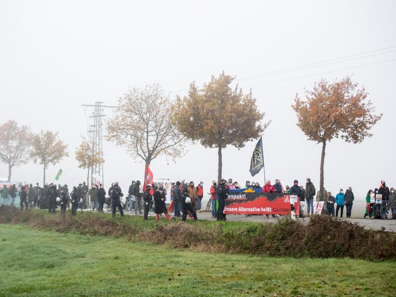 Gegendemonstranten haben sich auf einer Landstraße versammelt. Foto: Marcel Kusch/dpa