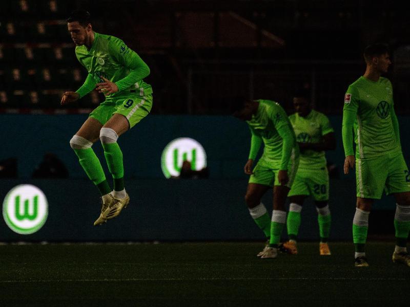 Das Logo vom VfL Wolfsburg leuchtet vor Spielbeginn auf Werbebanden, während die Spieler das Spielfeld betreten. Foto: Swen Pförtner/dpa