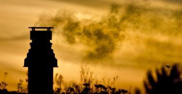 Ein kleiner Schornstein auf einem bepflanzten Dach entlässt bei Sonnenaufgang die Abgase einer Gasheizung in die eiskalte Morgenluft. Foto: picture alliance / dpa