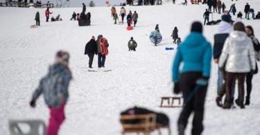 Ausflügler ziehen ihre Schlitten einen verschneiten Hang hoch. Die Stadt Winterberg bittet wegen der Corona-Pandemie auf Besuche in dem Wintersportort und an den Pisten im Sauerland zu verzichten. Foto: Marius Becker/dpa