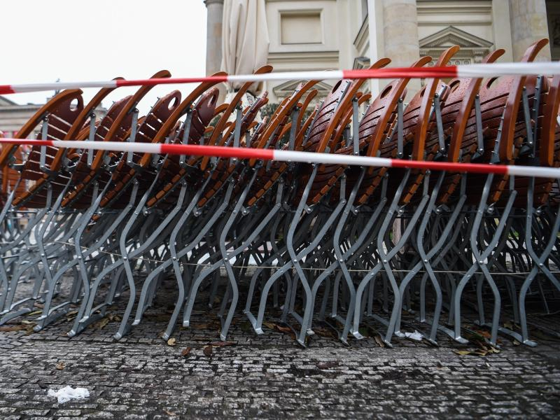 Auf dem Gendarmenmarkt in Berlin stehen zusammengestapelte Stühle hinter einem Absperrband. Foto: Kira Hofmann/dpa-Zentralbild/dpa