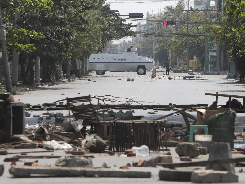 Ein gepanzertes Polizeifahrzeug fährt während des Protests gegen den Militärputsch an auf der Straße liegenden Trümmern vorbei. Foto: Uncredited/AP/dpa