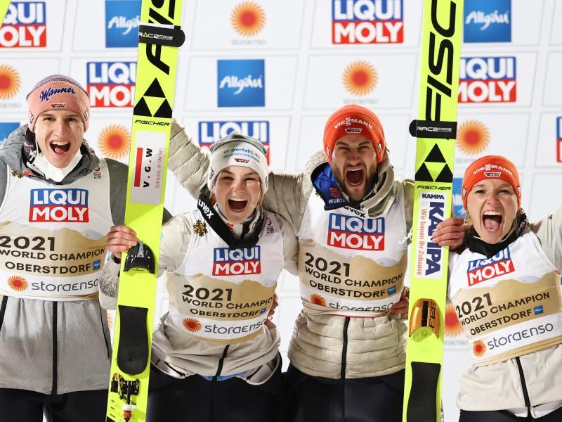 Karl Geiger, Anna Rupprecht, Markus Eisenbichler und Katharina Althaus (l-r) feiern die Goldmedaille bei der Heim-WM in Oberstdorf. Foto: Daniel Karmann/dpa