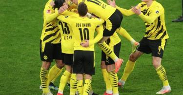 Dortmunds Spieler bejubeln das Führungstor von Julian Brandt (verdeckt). Foto: Friedemann Vogel/EPA-Pool/dpa