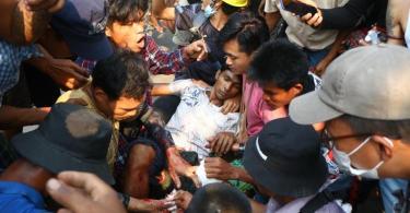 Demonstranten umringen einen Verletzten bei einem Protest gegen den Militärputsch in Yangon. Foto: Uncredited/AP/dpa