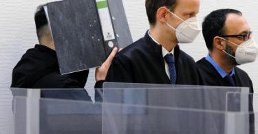 Der Angeklagte verbirgt im Sitzungssaal des Landgerichts Ingolstadt sein Gesicht hinter einem Aktenordner. Davor stehen seine Verteidiger. Foto: Ulf Vogler/dpa/Archiv