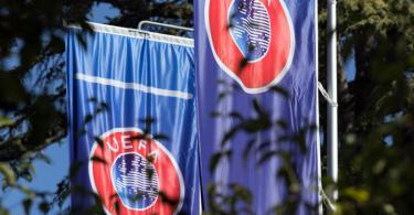 Flaggen mit dem Logo der UEFA wehen im Garten des Hauptquartiers der Union. Foto: Soeren Stache/dpa